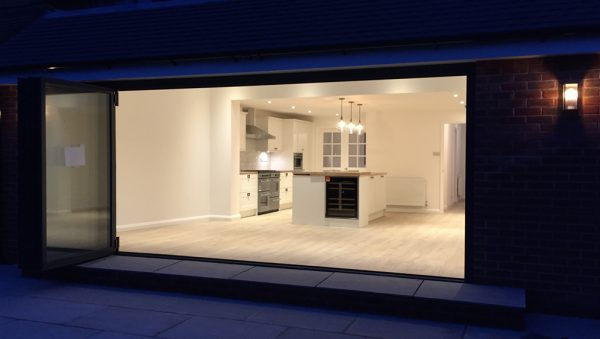 Property alteration showing finished extension and sliding doors at night